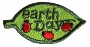 "On an oval emblem, the text ""earth day"" is stitched in dark-green. Three lady-bugs are walking around the text in a lighter green oval."