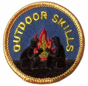 "Two humans are stitched in silhouette. Behind them a campfire crackles and the words ""Outdoor Skills"" is stitched in an arc above."